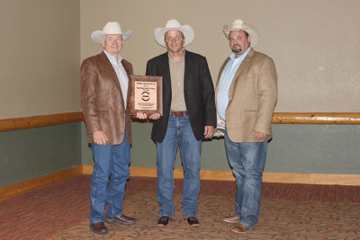 Wagonhound Land and Livestock was honored as the 2015 Commercial Producer of the Year at the Red Angus Association of America National Convention. Craig Bieber, pictured far right, presented the award to Art Nicholas and Dustin Ewing.
